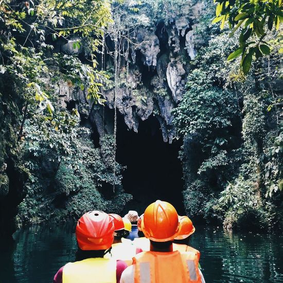 Rear View Of People On Boat In River Entering Cave