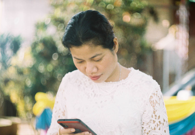 Woman using mobile phone while standing outdoors
