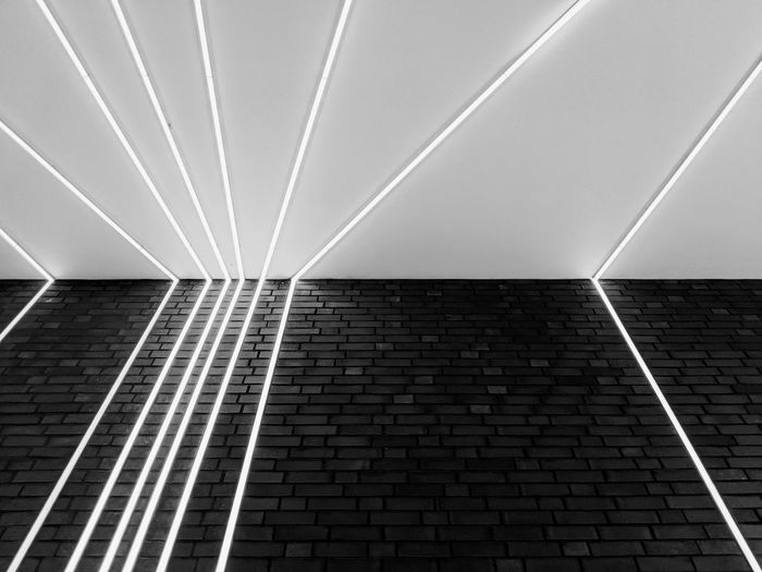 Low angle view of illuminated fluorescent lights on wall and ceiling