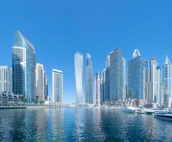 Modern buildings by swimming pool against sky in city