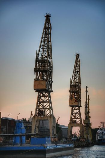 Cranes at commercial dock against sky