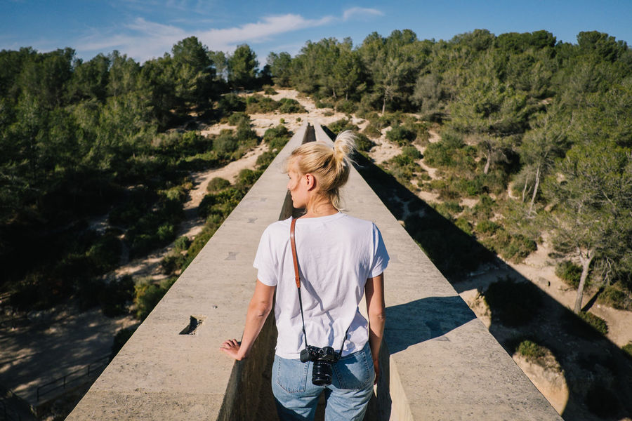 Aqueduct Architecture Rome Beauty In Nature Bridge Casual Clothing Day Leisure Activity Les Ferreres Aqueduct Lifestyles Mountain Nature Old One Person Outdoors Real People Rear View Scenics Sky Standing Sunlight Tree Young Adult Young Women Press For Progress