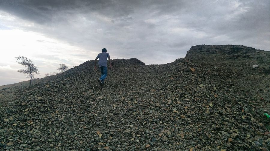 Low angle view of man walking on hill against cloudy sky during sunset