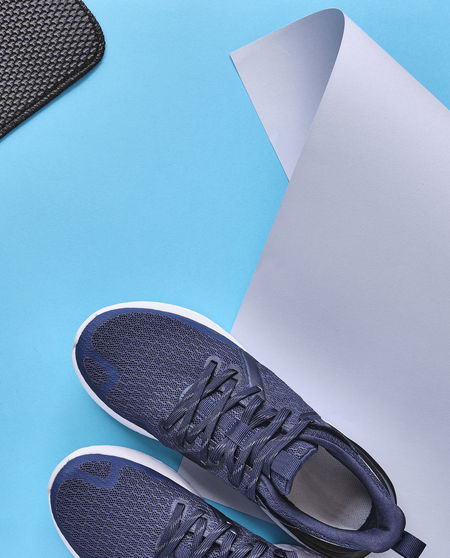 High angle view of shoes on floor against blue background