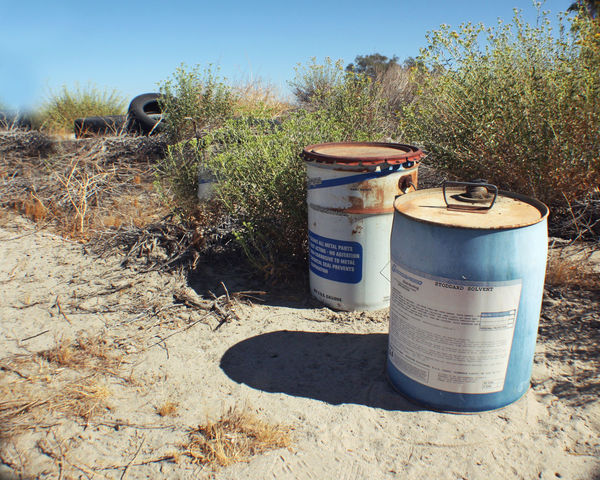 Junk Trash Abandoned Barrel Clear Sky Day Desert Junk Drum - Container Field Grass Growth Industrial Chemicals Landscape Nature No People Outdoors Sky Solvents Sunlight Tree
