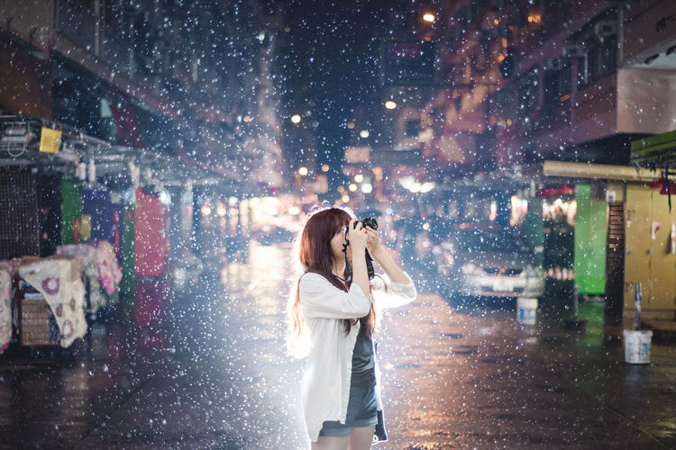 Woman standing on wet street in city