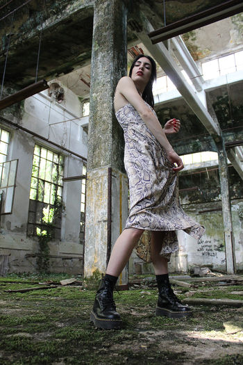 Full length portrait of woman standing in abandoned building