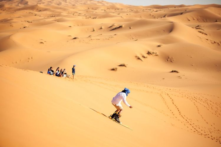 Person sandboarding in desert against clear sky
