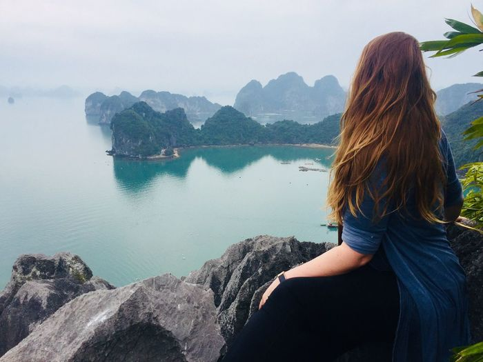 Woman looking at sea while sitting on mountain