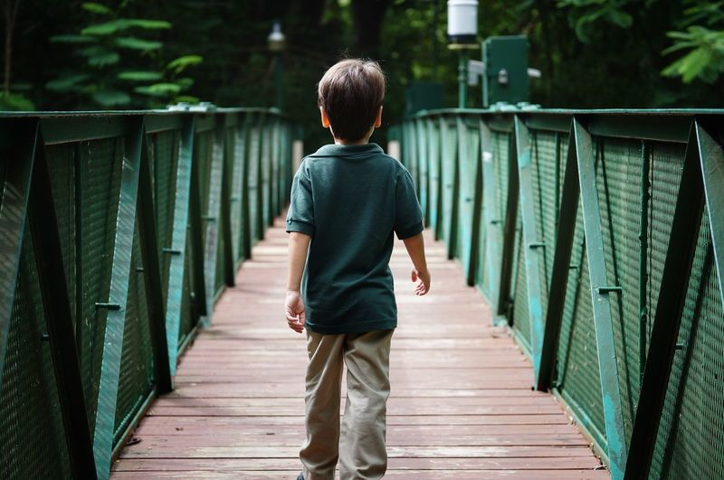 Rear view of boy walking on footbridge