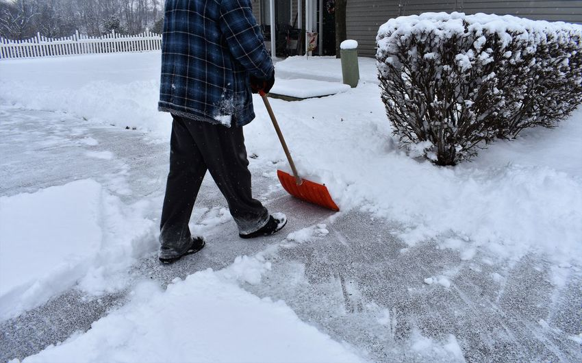 Low section of man cleaning on snow covered yard