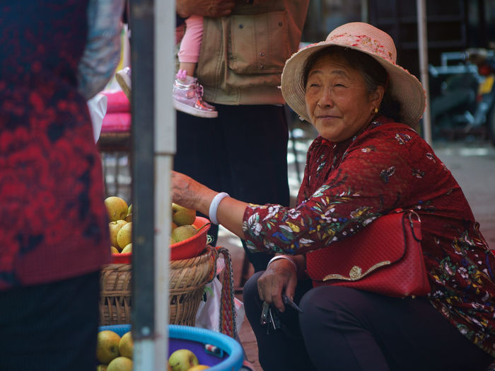 Full length of woman sitting at market