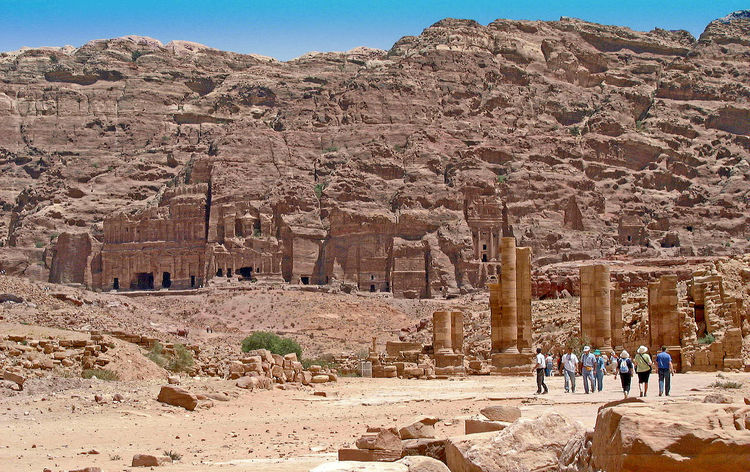 Foreground are the remains of the Roman city and behind the Royal Nabataean rock tombs - Petra, Jordan Petra (Arabic: البتراء, Al-Batrāʾ; Ancient Greek: Πέτρα), originally known as Raqmu (Nabataean Arabic: الرقيم), is a historical and archaeological city in southern Jordan. Petra lies on the slope of Jabal Al-Madbah in a basin among the mountains which form the eastern flank of Arabah valley that run from the Dead Sea to the Gulf of Aqaba. Established possibly as early as the 4th century BC as the capital city of the Nabataean Kingdom. The Nabataeans were nomadic Arabs who invested in Petra's proximity to the trade routes by establishing it as a major regional trading hub. In AD 106 Petra was annexed by the Roman empire. Rome's diversion of the caravan trade and some devastating earthquakes in subsequent centuries put the city into decline. Nabataean Kingdom Petra Jordan Roman Ruins Ancient Ancient Architecture Ancient Civilization Archaeology Architecture Arid Climate Built Structure Day Desert Desert Location History Large Group Of People Leisure Activity Lifestyles Men Mountain Nature Old Ruin Outdoors Real People Rock - Object Rocky Mountains Sunlight Tourism Travel Travel Destinations Women