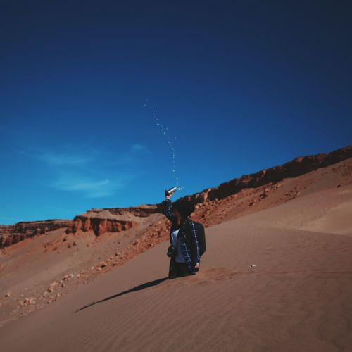 Woman throwing water while standing in sand against blue sky