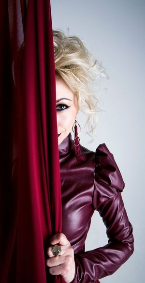 Portrait Of Woman Hiding Behind Curtain Against Gray Background