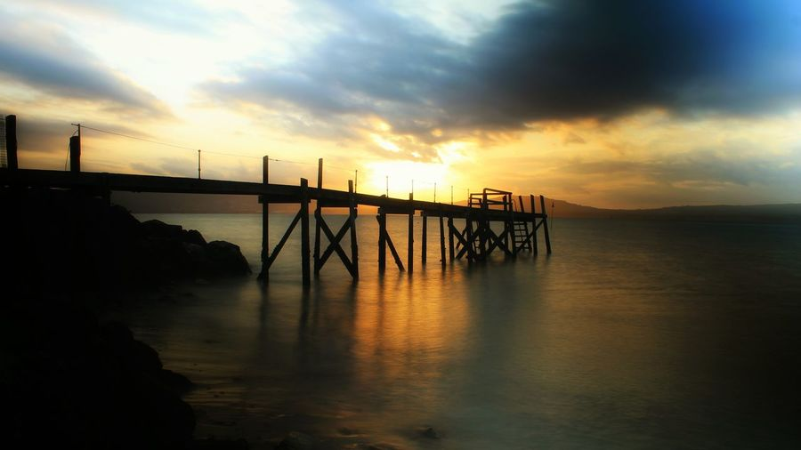 Scenic view of pier at sunset