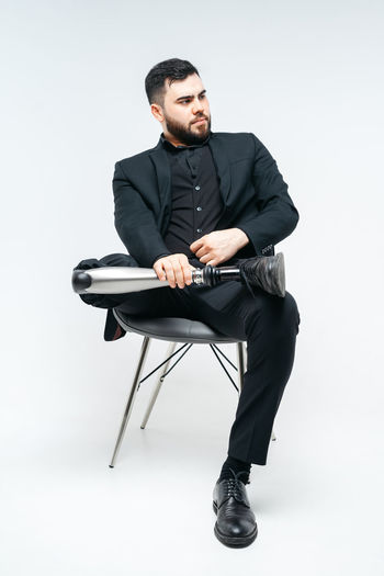Young man sitting on chair against white background