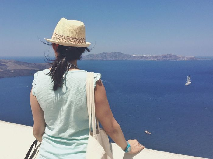 Rear view of woman standing by retaining wall against sea at santorini
