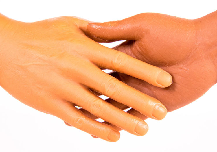 Close-up of woman with hands against white background