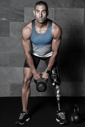 Sportive man with prosthesis training with kettlebell Adult Athletic Lifting Man Activity Amputation Athlete Confident  Exercising Front View Gym Healthy Lifestyle Inspiration Kettlebell  Looking At Camera Muscular Build One Person Outdoors Photograpghy  Portrait Prosthesis Standing Strength Strong Workout Young Adult