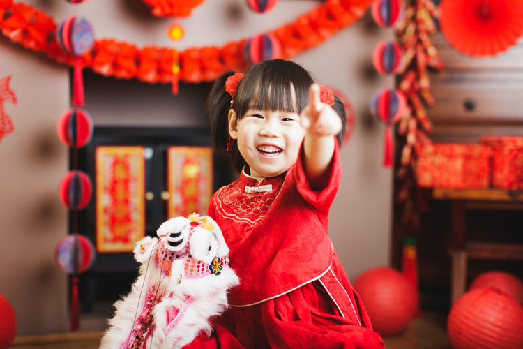 Portrait of smiling girl pointing at home