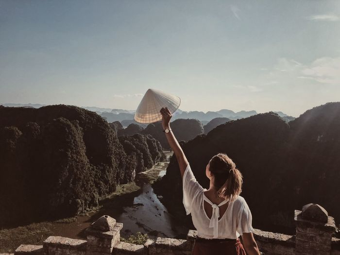 Rear view of woman with arms raised holding conical hat while standing on mountain against sky
