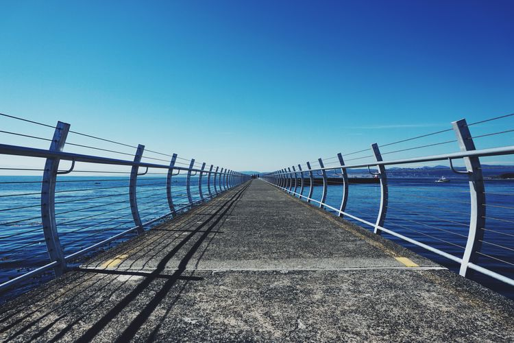 Beauty In Nature Blue Clear Sky Nature Ocean One Point Perspective Outdoors Pathway Pier Point Of View Railing Scenics Sea Seawall Sky Symmetry Vanishing Point Walkway Water