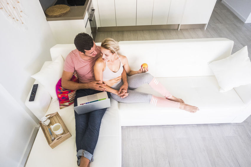 aerial point of view from above for caucasian nice couple in love sitting on the sofa at home and using a laptop together working or watching a movie. happy modern healthy lifestyle for millennial people Togetherness Indoors  Couple - Relationship Two People High Angle View Casual Clothing Men Women Adult Real People Bonding Love Young Women Young Adult Lifestyles Positive Emotion Heterosexual Couple Leisure Activity Sitting Relaxing Watching Caucasian 20 Years  25-29 Years Aerial View