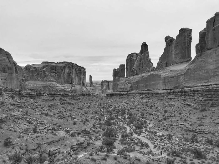 Low angle Black and white landscape of massive vertical rock formations at Arches National Park Arches National Park, Utah Rock Formation Black And White Sky Nature Day Land No People Outdoors Landscape Environment Field Rock Cloud - Sky Scenics - Nature