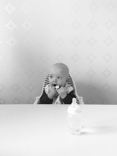 Baby sitting in high chair at home