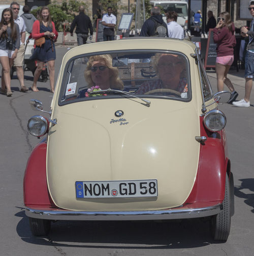 Couple driving a german BMW Isetta 300 on the promenade of Saint-Tropez, France. This bubblecar was produced from 1956 – 1962. The maximum speed was 85 km/h (53 mph) and in Germany the Isetta could be driven with a motorcycle license. BMW Isetta City Street Classic Car Driving German Isetta Memories Retro Transportation Bmw Bubble Car Bubblecar Car Collector's Car Front View Germany Land Vehicle Number Plate Oldtimer Outdoors People Small Street Vintage Vintage Cars