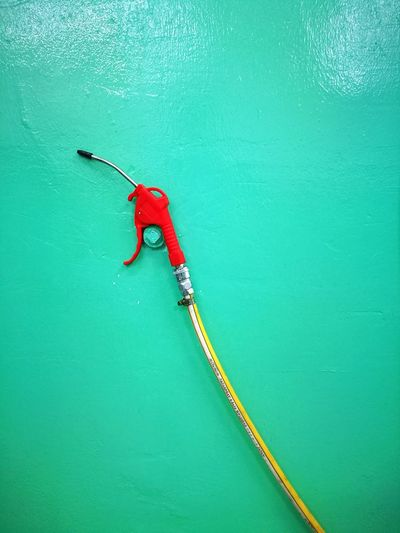 Hose hanging on turquoise wall