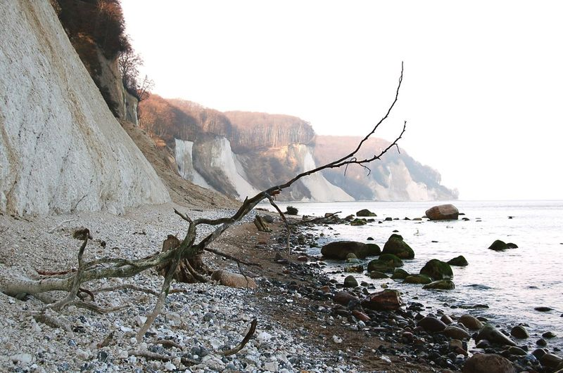 Chalk cliff by sea against sky
