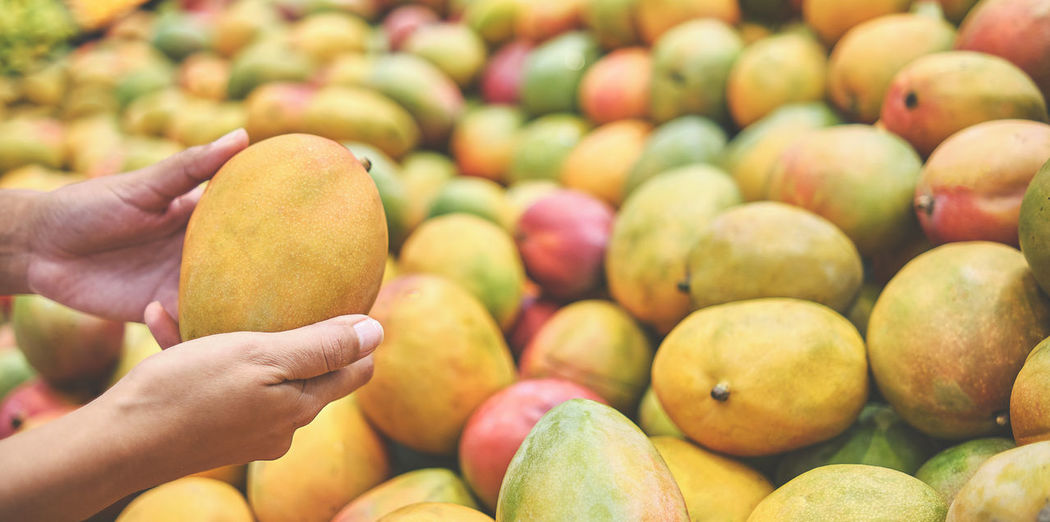 Close-up of hand holding fruits for sale at market stall