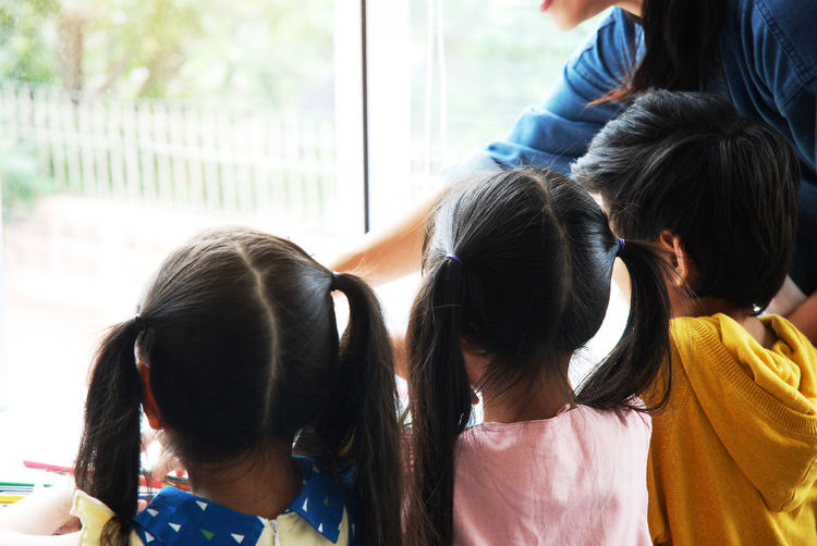 Rear View Of Children With Teacher In Classroom
