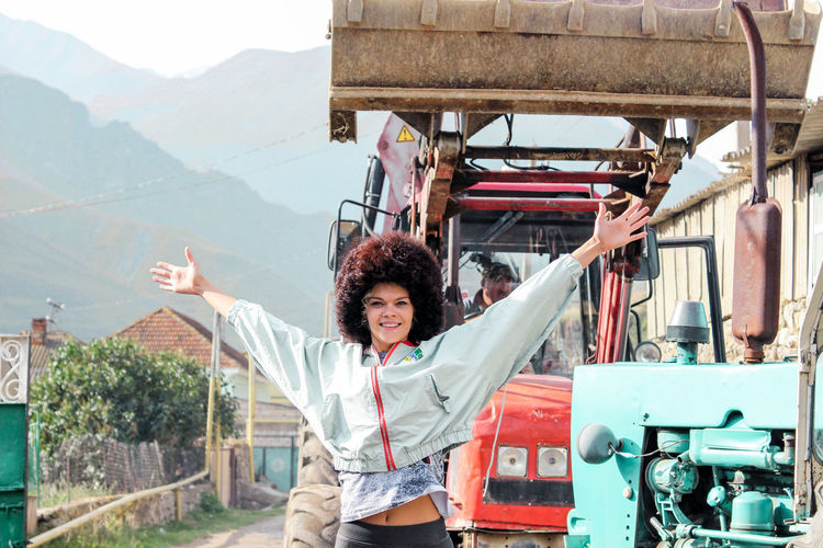 Portrait Of Smiling Young Woman With Arms Raised Standing Against Earth Mover