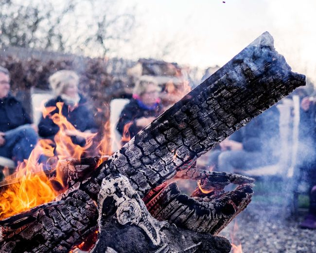 Close-Up Of Burning Wood Against People