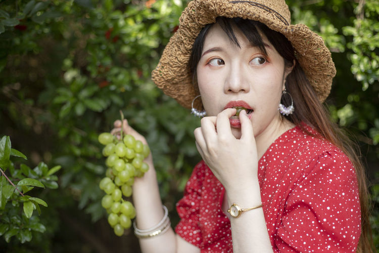 Woman with hat eating grapes while holding bunch by plants