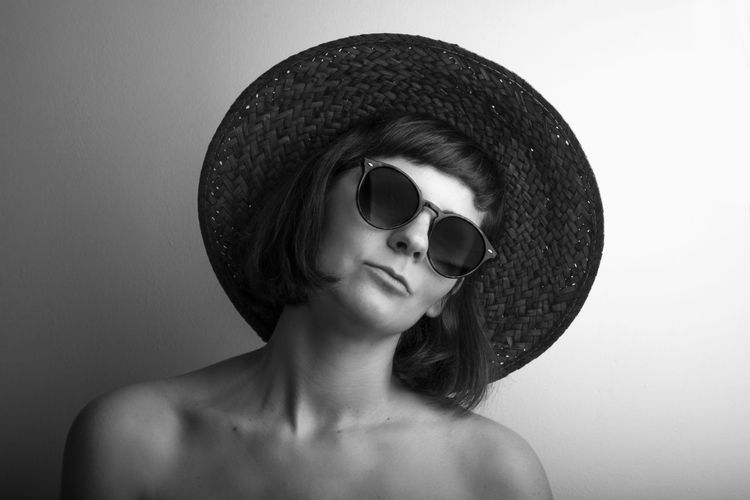 Portrait Of Young Woman Wearing Sunglasses And Hat Against Wall