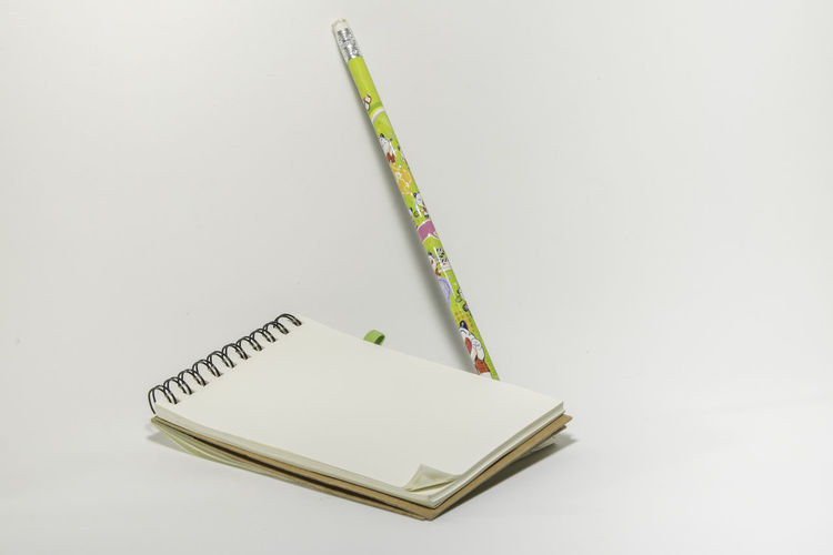 Close-up of note pad and pencil on white background