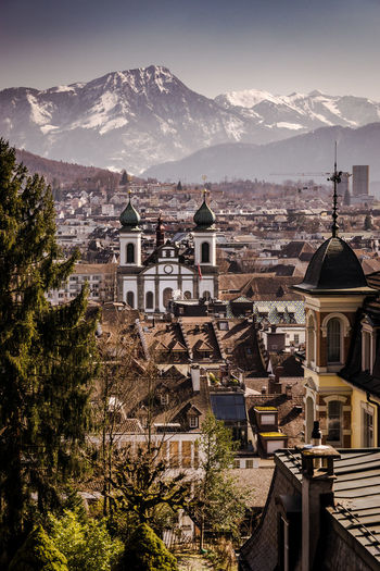 Lucerne, Switzerland - view on Jesuit Church Church Jesuits Church Lucerne Lucerne, Switzerland Spirituality TOWNSCAPE Outdoors Spire  Cityscape Travel Destinations No People Residential District Mountain Range City Place Of Worship Religion Building Mountain Architecture Building Exterior Tree