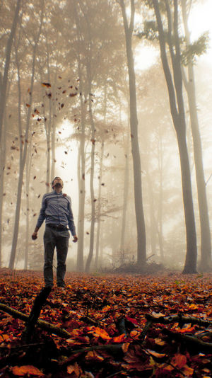 Full length of man standing with leaves in mid-air at forest during autumn