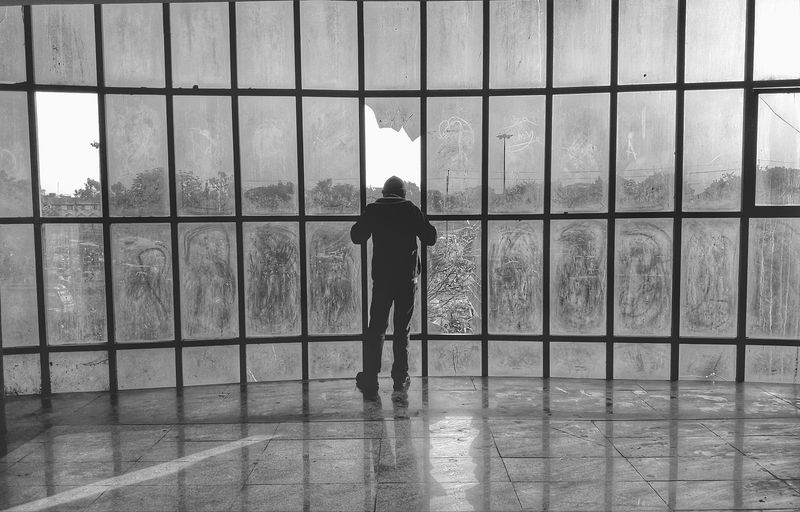 Rear view of man standing against window