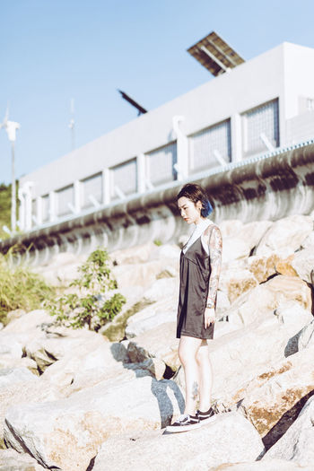 Side view of thoughtful young woman standing on rocks on sunny day