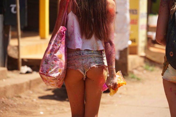 Midsection of messy young woman standing on road