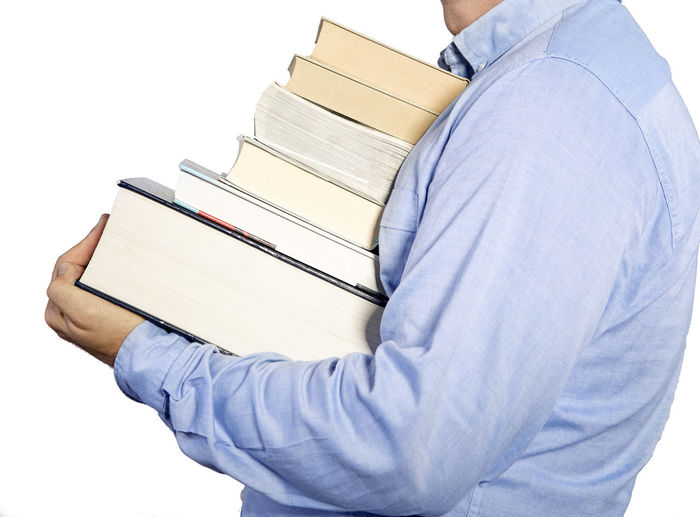 Midsection of man carrying books against white background