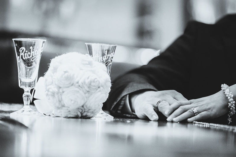 Cropped image of bride and groom by table with wineglasses