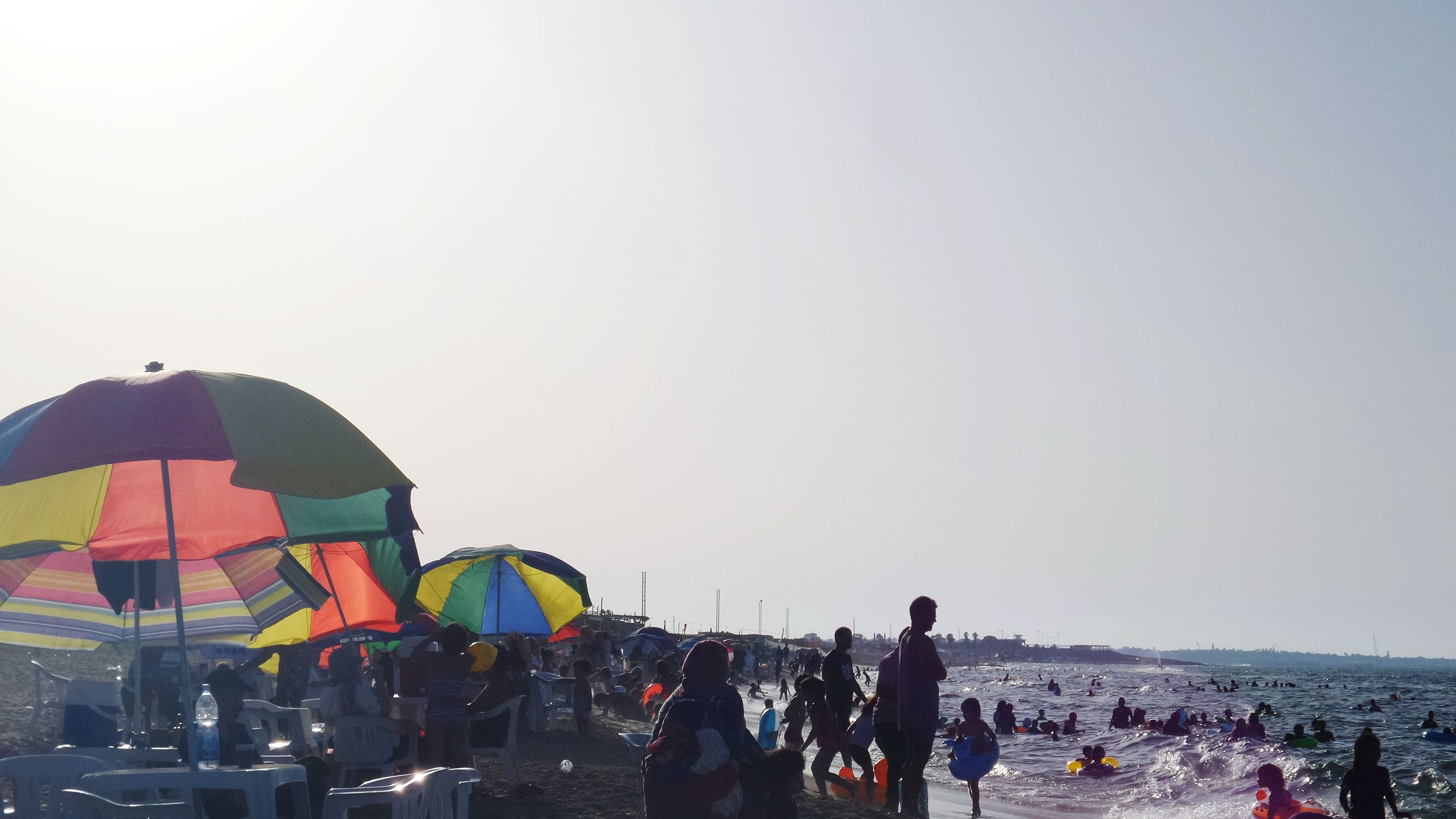 clear sky, leisure activity, lifestyles, large group of people, copy space, water, men, person, sea, enjoyment, mixed age range, vacations, sky, tourist, outdoors, horizon over water, medium group of people, nature, fun
