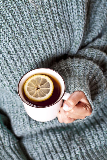 Female hands holding mug of hot tea with lemon in morning. young woman relaxing tea cup on hand.