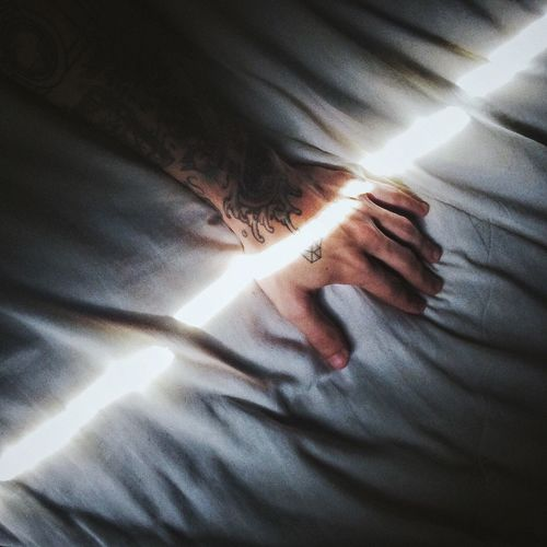 Cropped image of man hand on bed with sunlight